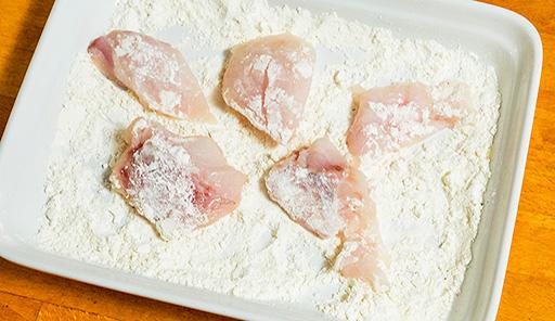 調理工程01_白身魚に塩・こしょうを振って味をつけ、小麦粉をまぶす