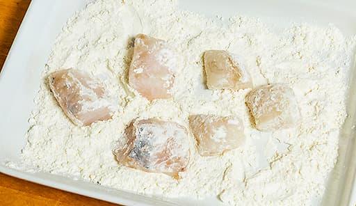 調理工程01_魚に小麦粉をまぶしてはたき、きつね色になるまで揚げる