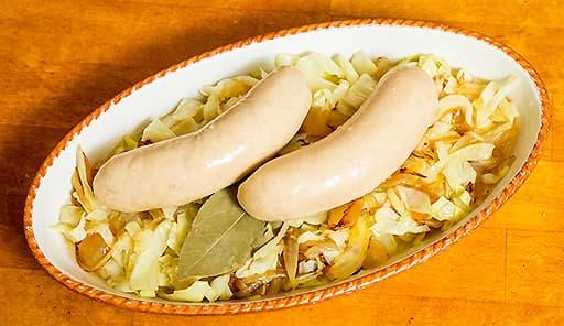 調理工程05_耐熱皿に炒めたキャベツ・たまねぎを敷いて、上にソーセージを乗せる