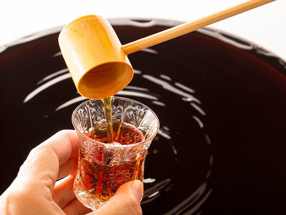 イメージ写真_瓶に入ったお酢から杓子でコップに注ぐ