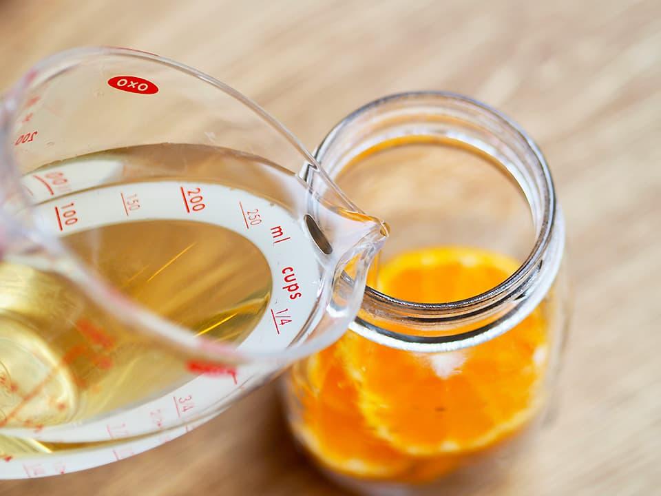 調理工程_みかん酢_輪切りにしたみかんを瓶に入れてお酢を注ぐ