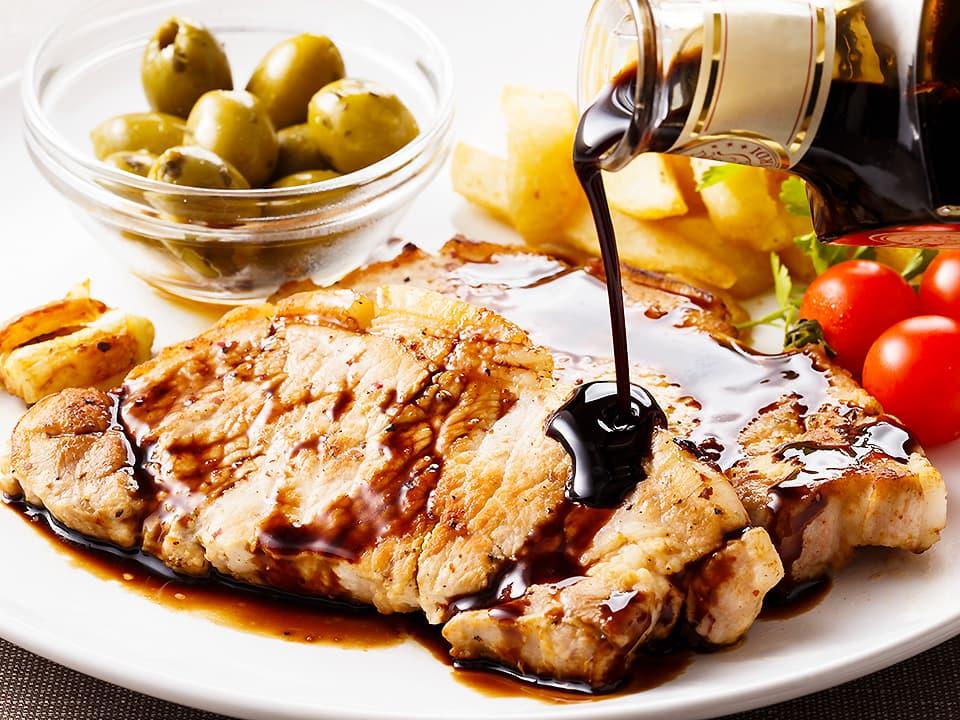 料理写真_お皿に盛り付けたお肉にバルサミコ酢をかける