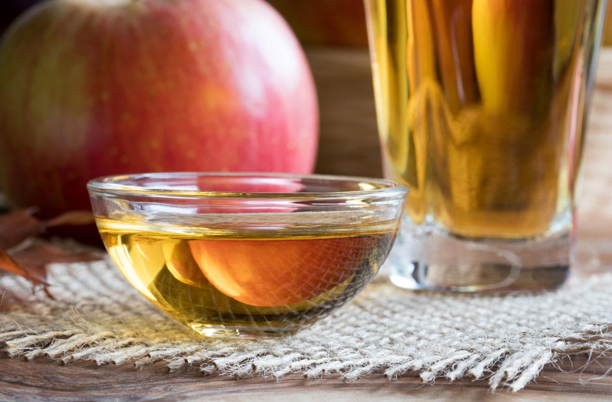 りんご酢とりんご、りんご酢ドリンクが置かれている様子